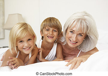 Grandmother Relaxing On Bed With Grandchildren