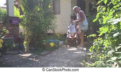 grandmother seats blonde toddler into pram  near house