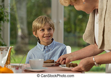 Grandmother serving homemade cake - Horizontal view of...