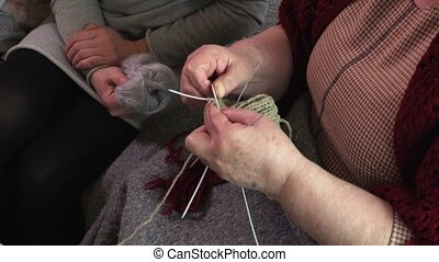 Grandmother siting on coach and knitting