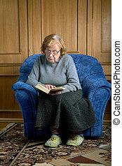 grandmother sits in an armchair and reads