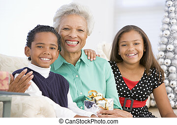 Grandmother Sitting With Her Two Grandchildren, Holding A Christm