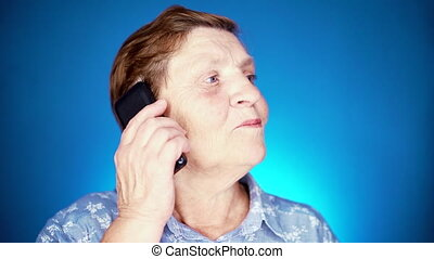 Grandmother smiling, have pleasant conversation. slow motion. Elderly woman talking with mobile device on blue studio wall.