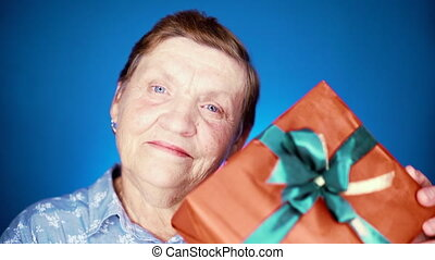 Grandmother smiling, she happy to get gift box with bow on her birthday or Christmas. Elderly woman pensioner on blue background.