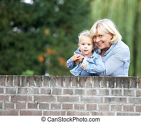 Grandmother smiling with baby girl outdoors