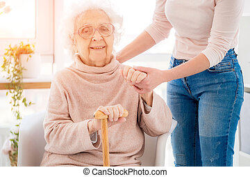 Grandmother supported by woman