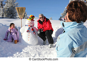 Grandmother taking a picture of her family and their snowman