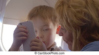 Grandmother talking to grandson in the plane