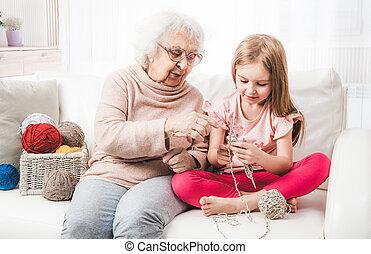 Grandmother teach granddaughter knitting