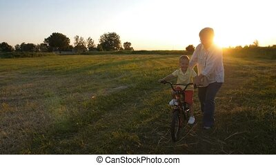Grandmother teaching grandson to ride a bike