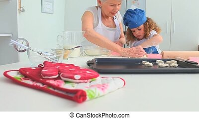Grandmother teaching her grand daughter how to bake