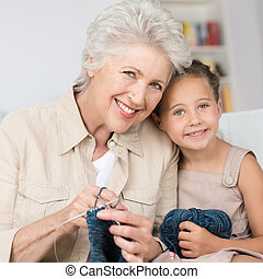 Grandmother teaching her granddaughter to knit