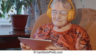 Grandmother using touch pad in wireless headphones - Elderly...
