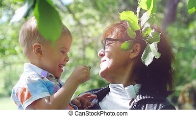 Grandmother wearing glasses and her little cute grandson enjoying sunny day in the park in slow motion. Happy childhood. 1920x1080