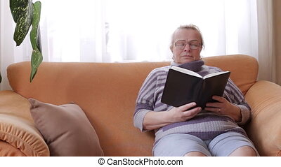 Grandmother wearing glasses reads a book and sitting on the sofa