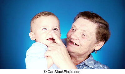 Grandmother with baby boy ion blue wall background having fun, smiling, playing. Grandson is happy to communicate with elderly great-grandmother