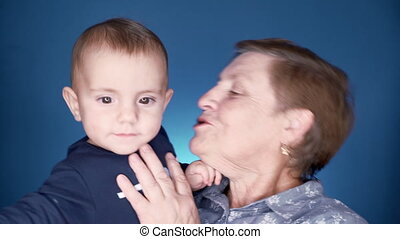 Grandmother with baby boy on blue wall background having fun, smiling, playing. Grandson is happy to communicate with elderly great-grandmother