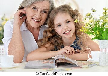 Grandmother with girl reading magazine
