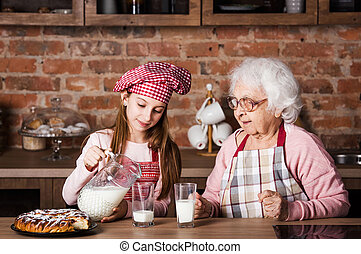 Grandmother with granddaughter drinking milk