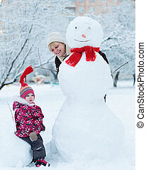 Grandmother with granddaughter playing in snow