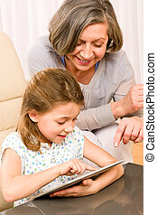 Grandmother with granddaughter use touch tablet