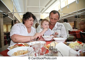 Grandmother with grandfather nourish child in canteen one