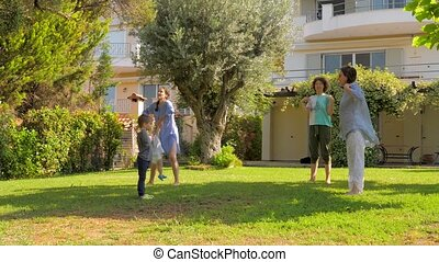 Sport during quarantine, coronavirus, covid-19. Family doing exercises on backyard. Healthy lifestyle. Morning exercises on front yard, garden. Sport outdoor. Family spending time together