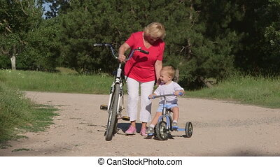 Grandmother with grandson riding bicycles in the summer park