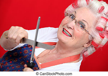 grandmother with hair curlers sharpening knives against red...