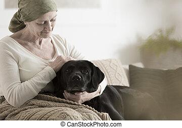 Grandmother with headscarf stroking dog - Sick grandmother...
