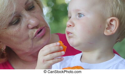 Grandmother with her grandchild eating apricot outdoors