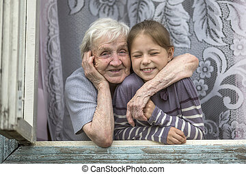 Grandmother with her granddaughter looking out the window of...