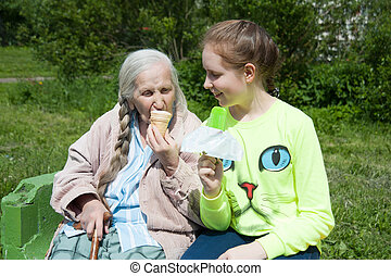 grandmother with her granddaughter, eating ice cream in the...