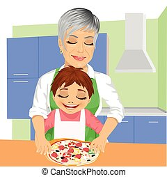 Grandmother with her grandson preparing delicious pizza together in kitchen
