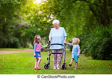 Grandmother with walker playing with two kids - Happy senior...