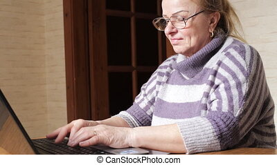 Grandmother works on a laptop sitting at table. Granny with computer