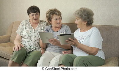 Grandmothers look at photos using digital tablets