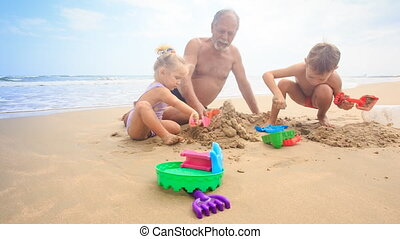 Grandpa Kids Build Sand Castle on Beach by Wave Surf