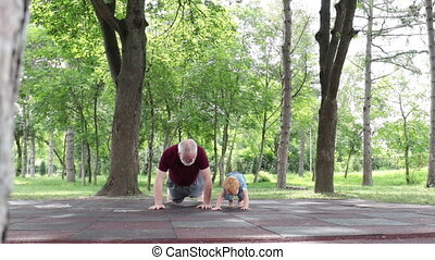 Grandpa playing and jumping with his grandson in the park