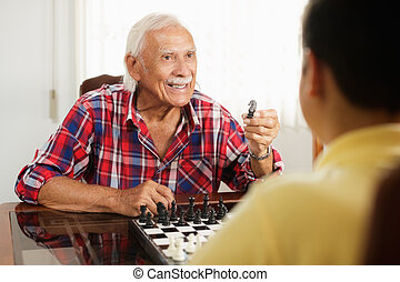 Grandpa Playing Chess Board Game With Grandson At Home