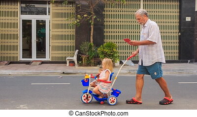 Grandpa Pushes Tricycle with Little Girl Reads Smartphone