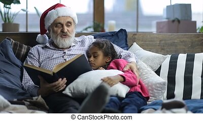 Grandpa reading bedtime story to sleepy child