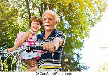 Grandpa riding bicycle with granddaughter in hands - Grandpa...