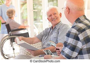 Grandpa talking to his friend - Smiling grandpa sitting with...