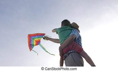 Grandpa teaching grandsonto fly kite - Low angle view of...