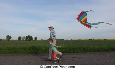 Grandpa with boy running with kite in countryside - Side...