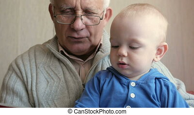 Grandpa with glasses reading a book beautiful baby. The child listens attentively to the tale. The boy about a year.