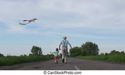 Grandpa with grandson flying kite in countryside - Back view...