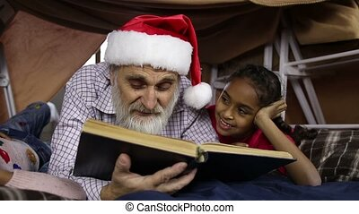 Grandpa with kids reading fairy tales on Xmas Eve -...