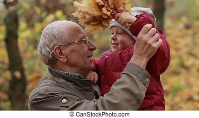 Grandpa with toddler boy resting in autumn park